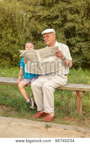 Senior man and bored child reading newspaper outdoors