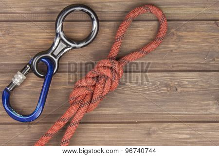 Figure eight knot with climbing carabiner and rappel eight on wooden background.