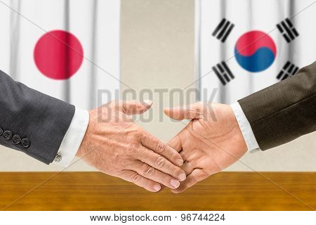 Representatives Of Japan And South Korea Shake Hands