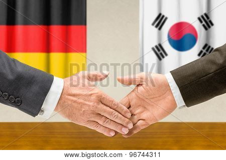 Representatives Of Germany And South Korea Shake Hands