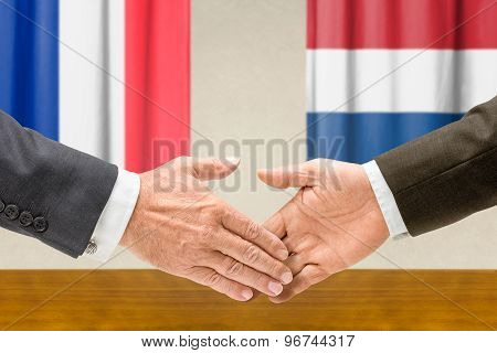 Representatives Of France And The Netherlands Shake Hands