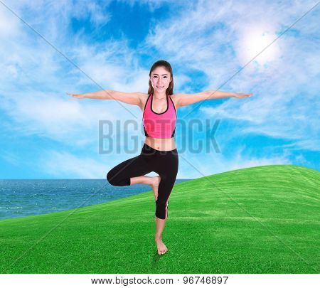 Woman Doing Yoga Exercise On Grass With Sky