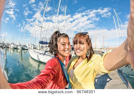 Young Women Girlfriends Taking A Selfie At Harbour Docks With Sailboats - Concept Of Friendship