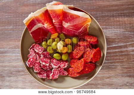 Tapas of Spain with ham olives sausage and chorizo on wooden background