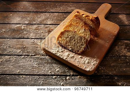 Bread sliced loaf on wooden board in rustic wood table