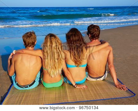 friends group couples sitting in beach sand rear view back looking to the sea