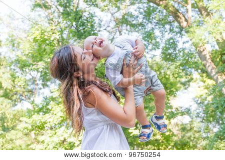 happy young mother with child - baby boy - outdoor portrait on green natural background