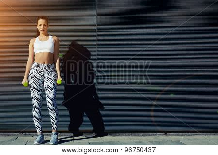 Attractive female taking break while working on her arms outdoors with copy space for your text