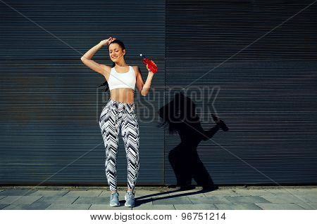 Happy female runner hold water bottle while standing against black wall background outdoors