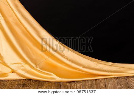 Golden satin on wooden table.