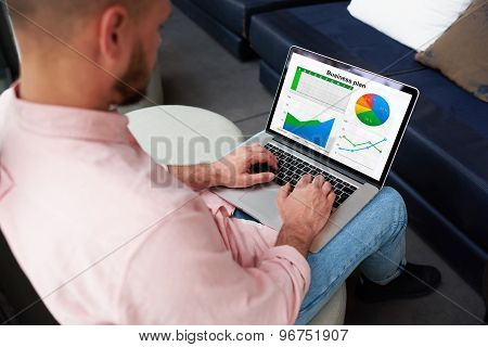 Businessman sitting front laptop computer with financial information as graphics and charts