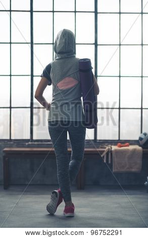 Woman Standing Relaxing In Gym Seen From Behind Wearing Hoodie