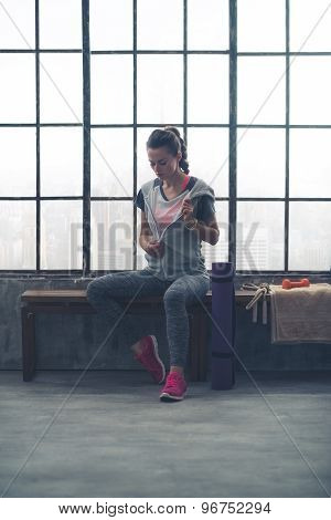 Woman Removing Sweatshirt While Sitting In Loft Gym