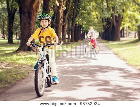 Two Boys Ride A Bicycle In Park