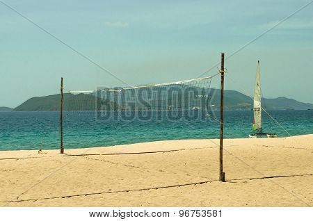 Volleyball Net And A Sailboat On The Beach