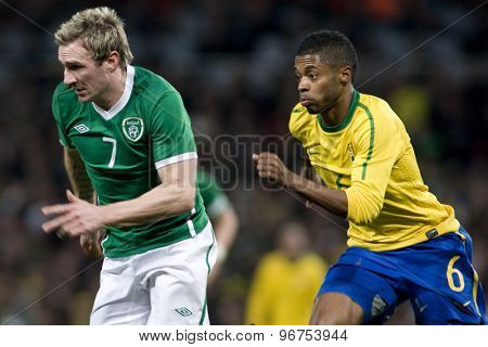 LONDON, ENGLAND. March 02 2010: Ireland's Liam Lawrence and Brazil's Michel Bastos during the international football friendly between Brazil and the Republic of Ireland played at the Emirates Stadium.