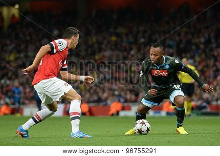 LONDON, ENGLAND - Oct 01 2013: Arsenal's midfielder Mesut Ozil from Germany and Napoli's defender Camilo Zuniga from Columbia during the UEFA Champions League match between Arsenal and Napoli.
