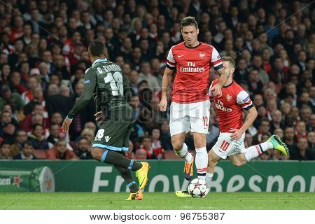 LONDON, ENGLAND - Oct 01 2013: Napoli's defender Camilo Zuniga and Arsenal's forward Olivier Giroud from France  compete for the ball during the UEFA Champions League match between Arsenal and Napoli.