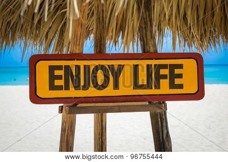 Enjoy Life sign with beach background