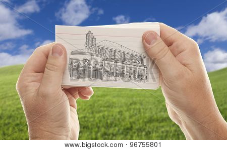 Male Hands Holding Stack of Paper With House Drawing Over Empty Grass Field and Sky.
