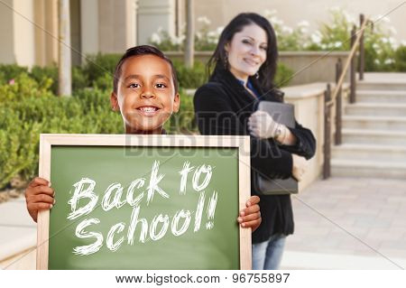 Happy Hispanic Boy Holding Back to School Chalk Board Outside on School Campus as Teacher Looks On.