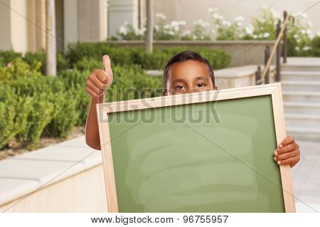 Happy Hispanic Boy with Thumbs Up Holding Blank Chalk Board Outside on School Campus.