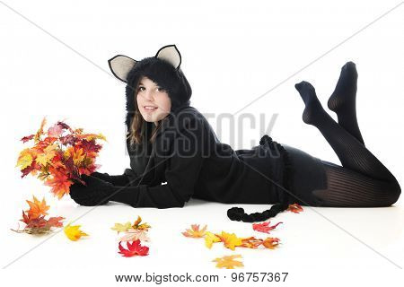 A beautiful teen girl in a black cat outfit, relaxed on her belly surrounded by colorful autumn leaves.  On a white background.