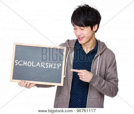 Young man finger point to chalkboard showing a word scholarship