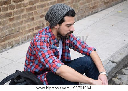 Young Stylish Student Seated On The Street.