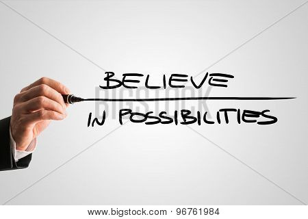 Closeup Of Male Hand Writing An Inspirational Message Believe In Possibilities From Behind A Grey Vi
