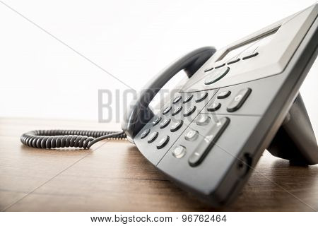 Black Landline Telephone Instrument With A Number Pad On A Rustic Wooden Desk