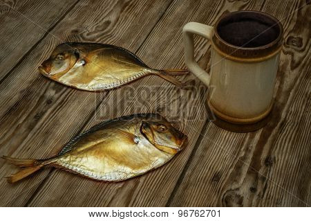 Two Smoked Fish And Beer Mug On A Wooden Table Close-up