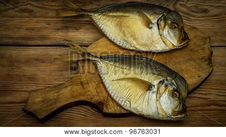 Two Smoked Fish On A Wooden Cutting Board Closeup