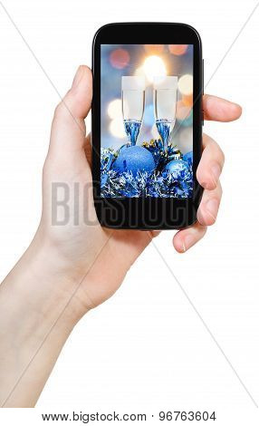 Hand Holds Cellular Phone With Xmas Still Life
