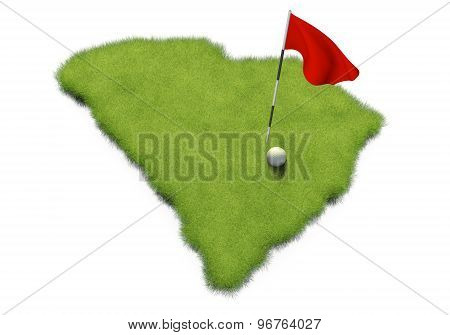 Golf ball and flag pole on course putting green shaped like the state of South Carolina