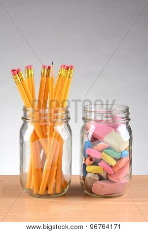 Closeup of two jars on a teachers desk with pencils and erasers. Vertical format on a light to dark gray background with copy space.