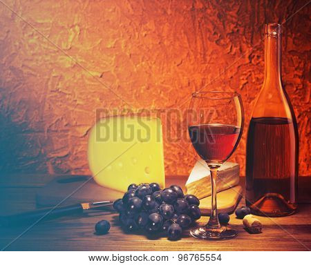Still-life with cheese, grapes and glass and bottle of red wine.Filtered image: vintage effect.
