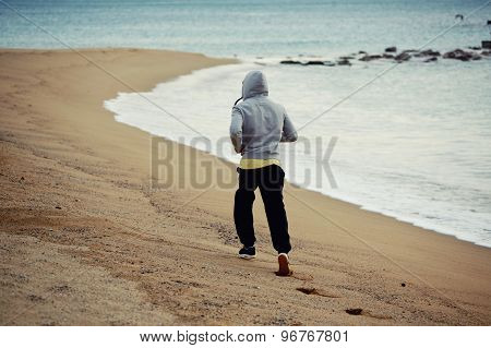 Sporty young man working out at early morning while run along the seashore over wet sand