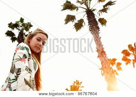 Low angle view attractive female in trendy cool clothing stand on palm trees and sky background