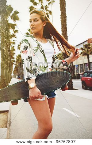 Young trendy long haired woman posing with her longboard enjoying good day in summer