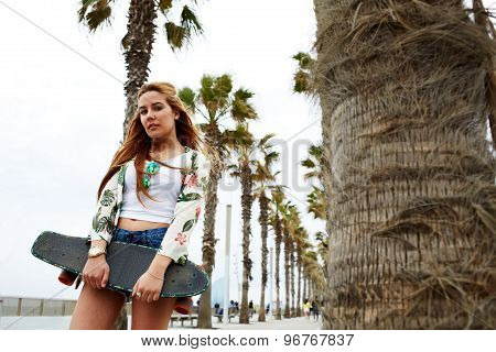 Portrait of cool trendy woman posing with her long board during recreation promenade in summer