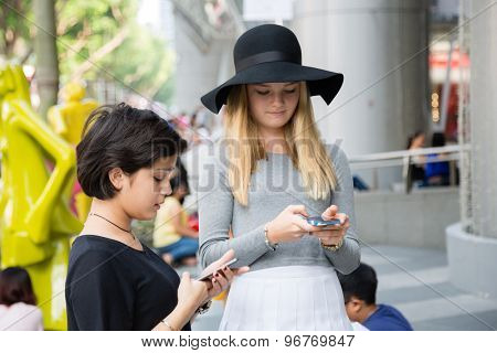SINGAPORE - CIRCA FEBRUARY, 2015: Children use smartphones at the mall ION Orchard - one the best shopping centers on Orchard Road. In the mall more than 300 shops of the famous brands.