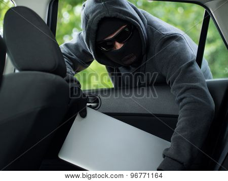 Car theft - a laptop being stolen through the window of an unoccupied car.
