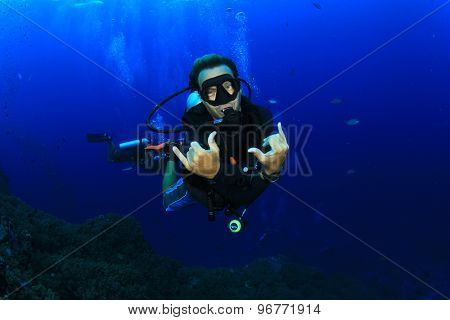 Scuba diving on tropical coral reef with fish underwater