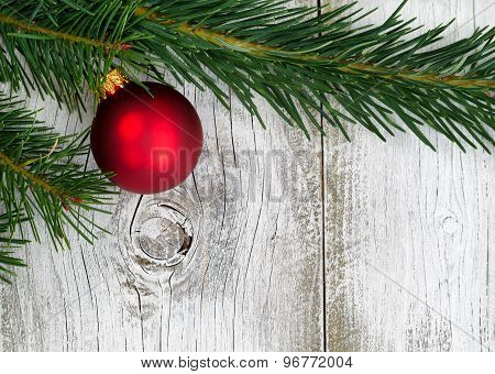 Grand Fir Branch With Singe Red Ornament On Rustic White Wooden Boards