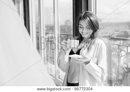 Beautiful Woman Drinking Coffee Sitting By The Window