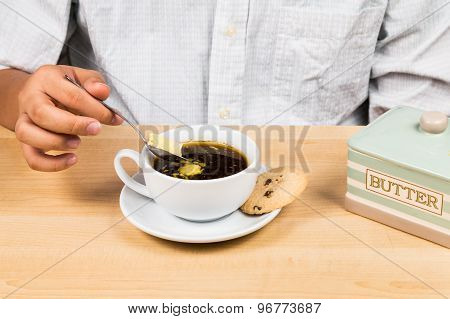 Person enjoying a cup of coffee with added butter