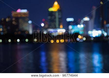 Abstract blurred bokeh at night of Bangkok business area with water reflection