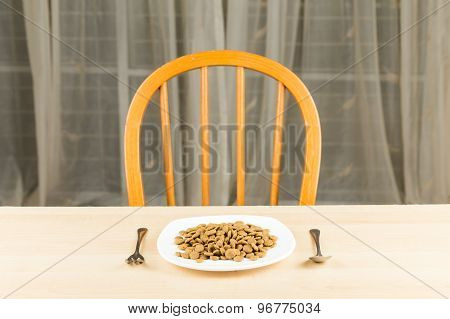 Dog food served on plate with fork and spoon