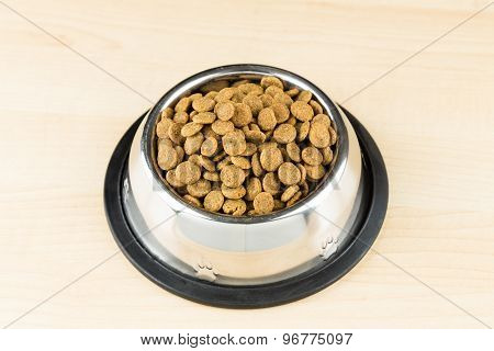 Dog Kibbles in a bowl on wooden floor